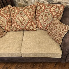 Reupholstery Brown sofa with cream seat cushions and patterned back cushions