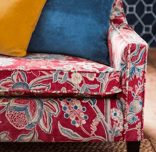 Reupholstery corner of a red large patterned sofa